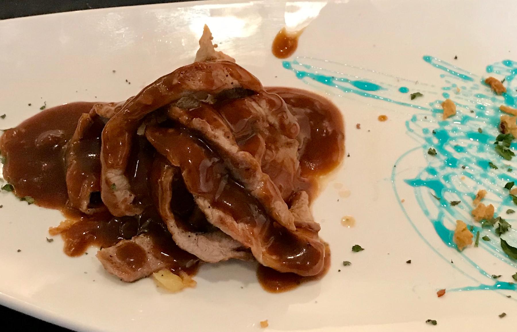 Fideos de presa macerada sobre patatas panadera, salsa cazadora y crujiente de cebolla